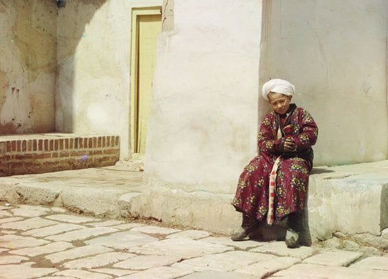 Un petit garçon assis dans la cour de la mosquée Tillia-Kari de Samarkand (Ouzbékistan actuel)